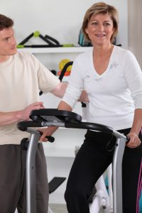 An older woman works out on a treadmill doing light exercise