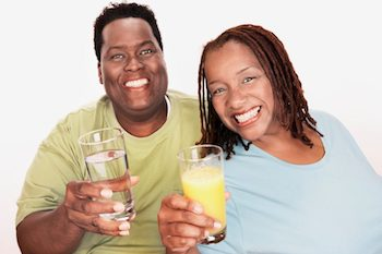 An African American couple holding beverages and smiling about their weight loss
